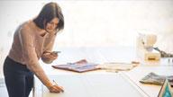 Frau zeichnet an einem Schreibtisch