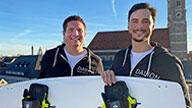 Zwei Männer halten ein Kiteboard