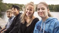Vier Jugendliche sitzen an einem See