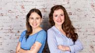 Zwei Frauen stehen vor einer Wand