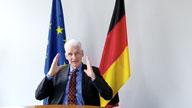 Ein Mann sitzt vor einer EU- und Deutschlandfahne